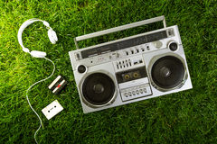 Retro-styled silver boom box, earphones and audio cassettes over Stock Photography