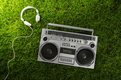 Retro-styled silver boom box and earphones over green grass stud Royalty Free Stock Images