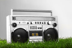 Retro-styled silver boom box over green grass isolated Stock Images