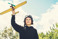 Retro styled vintage closeup portrait of smiling boy with plane royalty free stock photography
