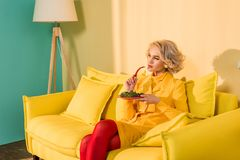 retro styled woman with broccoli on plate and chili pepper in hand resting on sofa at bright apartment, doll stock photography
