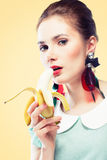 Retro styled woman eating banana Stock Photography