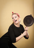Retro styled woman having fun with kitchen accessories. Royalty Free Stock Image