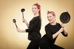 Retro styled women having fun with kitchen accessories. Royalty Free Stock Image