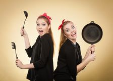 Retro styled women having fun with kitchen accessories stock photos