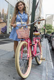 Retro styled young woman with blue dress and pink bicycle in city Royalty Free Stock Photography