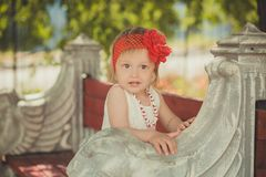 Retro stylish dressed blond young baby girl child posing in central park garden wearing french couturer white dress red bandana an stock photography