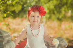 Retro stylish dressed blond young baby girl child posing in central park garden wearing french couturer white dress red bandana an stock photos