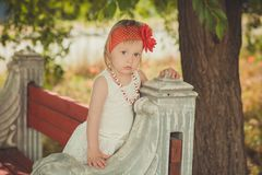 Retro stylish dressed blond young baby girl child posing in central park garden wearing french couturer white dress red bandana an stock image