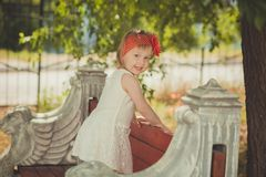 Retro stylish dressed blond young baby girl child posing in central park garden wearing french couturer white dress red bandana an royalty free stock photos