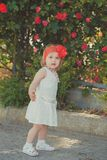 Retro stylish dressed blond young baby girl child posing in central park garden wearing french couturer white dress red bandana an royalty free stock image