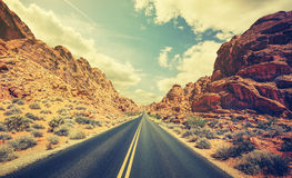 Retro stylized desert highway, travel adventure concept. Royalty Free Stock Photos