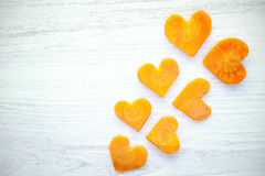 Retro stylized hearts made of carrot on grunge background. Royalty Free Stock Photo