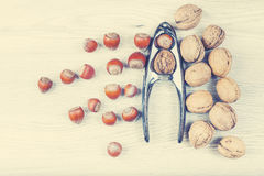 Retro stylized nuts with nutcracker on a wooden background. Stock Photos