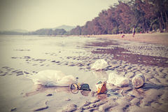 Retro stylized picture of garbage on a beach. Stock Photo