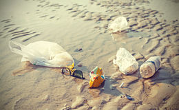 Retro stylized picture of garbage on a beach. Royalty Free Stock Photography