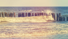 Retro stylized picture of wave crashing against wooden posts Stock Photography