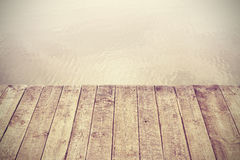 Retro stylized picture of wooden boards and lake. Royalty Free Stock Photography