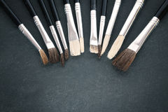 Retro stylized row of paintbrushes on old stone background. Royalty Free Stock Photos