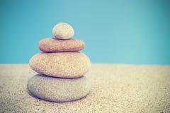 Retro stylized stone pyramid on sand, harmony and balance concep Royalty Free Stock Photo