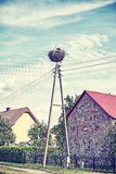 Retro stylized stork nest in a village. Royalty Free Stock Photography