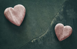 Retro stylized two wooden hearts on cracked stone background. Royalty Free Stock Photos