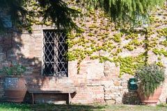 Retro stylowa fotografia ławka i kwiaty z a i ściana z cegieł Fotografia Royalty Free