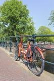 Retro stylowy bicykl blokował na bridżowym poręczu, Amsterdam, holandie Zdjęcie Royalty Free