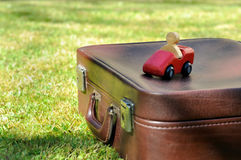 Retro suitcase and wooden toy. Wooden car on suitcase put in the grass Stock Photos