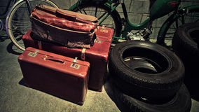 Retro  suitcases. 4 retro leather siutcases standing on the floor with bicycles and and car tires Stock Photography