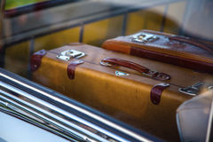 Retro suitcases in vintage car. Two retro suitcase in retro car. Suitcases in the trunk of a car close-up of retro. Suitcases can be seen through the window of Royalty Free Stock Photo