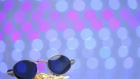 Retro sunglasses with shell and blurry shining colored background stock footage