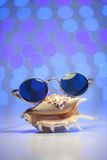 Retro sunglasses with shell and blurry shiny colored background. Retro sunglasses with shell and blurry colored background Royalty Free Stock Photo