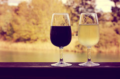 Retro sunset filter style image of two glasses of wine, white and red, on wooden rail Stock Photography