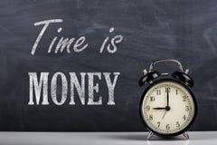 Retro sveglia e il ` del ` del testo Il tempo è denaro fotografia stock