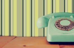 Retro- tadelloses Pastelltelefon auf Holztisch und abstraktem Retro- geometrischem Pastellmuster Hintergrund Retro- gefiltertes B Stockfoto