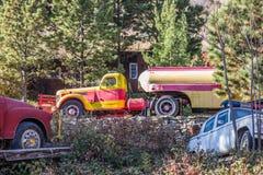 Retro Tanker Truck In Salvage Yard. Retro Yellow & Red Tanker Truck With Other Vehicles In Salvage Yard Royalty Free Stock Photos