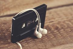Cassette with earphone. Retro tape cassette with earphone on table stock images