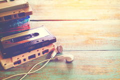 Retro tape cassette with earphone on wood table. Top view above shot of retro tape cassette with earphone on wood table - vintage color effect styles Royalty Free Stock Images