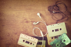 Retro tape cassette with earphone on wood table. Top view above shot of retro tape cassette with earphone on wood table - vintage color effect styles stock images