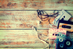 Retro tape cassette with earphone on wood table Royalty Free Stock Image