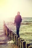 Retro tappning filtrerade bilden av den lyckliga flickan på stranden Arkivbild