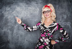 Retro teacher in glasses showing on something by finger. On blackboard background Stock Photography