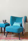 Retro teal armchair and matching ottoman with decor objects. Candles, scarf and book royalty free stock photography
