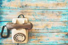 Retro- Technologie des Weinlesetelefons auf blauer Farbenfarbholztabelle stockbild