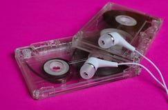 Retro- Technologie Transparente Audioplastikkassette und weiße Vakuumkopfhörer auf einem hellen rosa Hintergrund Lizenzfreies Stockbild