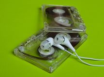 Retro technology. Plastic transparent audio cassette and white vacuum headphones on a bright green background. 80s Stock Photos