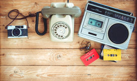 Retro technology of radio cassette recorder with retro tape cassette, vintage telephone and film camera on wood table. Stock Photo