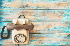 Retro technology of vintage telephone on blue paint color wood table. Stock Image