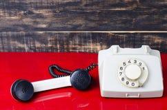 Retro telefon på ett skrivbord Fotografering för Bildbyråer